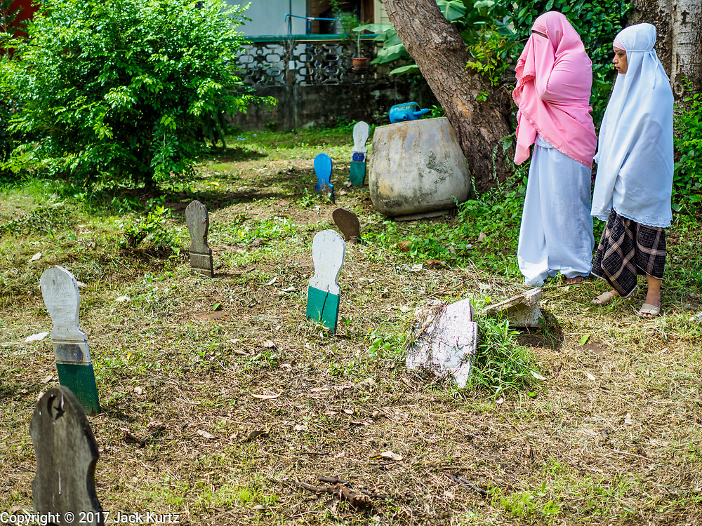 25 JUNE 2017 - BANGKOK, THAILAND: Women pray at the grave of a loved one after Eid al-Fitr services. It's customary in Thailand to clean the graves of family members after Eid al-Fitr. Eid al-Fitr is also called Feast of Breaking the Fast, the Sugar Feast, Bayram (Bajram), the Sweet Festival or Hari Raya Puasa and the Lesser Eid. It is an important Muslim religious holiday that marks the end of Ramadan, the Islamic holy month of fasting. Muslims are not allowed to fast on Eid. The holiday celebrates the conclusion of the 29 or 30 days of dawn-to-sunset fasting Muslims do during the month of Ramadan. Islam is the second largest religion in Thailand. Government sources say about 5% of Thais are Muslim, many in the Muslim community say the number is closer to 10%.    PHOTO BY JACK KURTZ