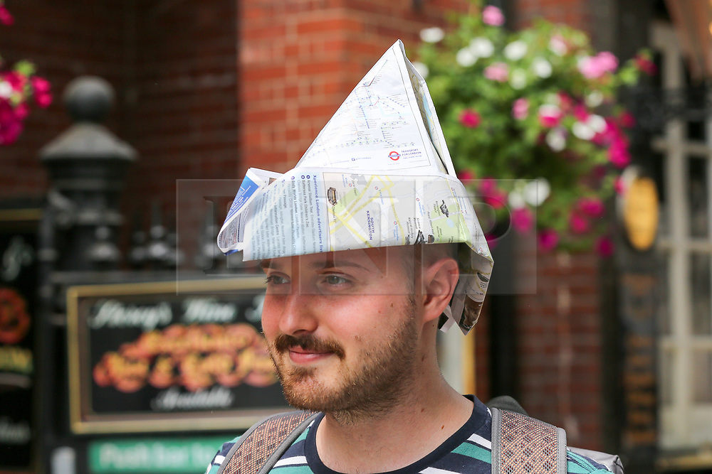 © Licensed to London News Pictures. 25/07/2019. London, UK. A tourist wearing a hat made from London maps shelters from the sun in Westminster on a hot and sunny day in London. According to the Met Office, today will be the hottest day of the year and temperatures are expected to break records. <br /> <br /> **Permission granted**<br /> <br /> Photo credit: Dinendra Haria/LNP