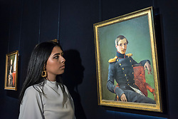 "© Licensed to London News Pictures. 31/05/2019. LONDON, UK. A staff member views ""Portrait of Alexander Nikolaevich Karamzin"", 1839, by Pimen Nikitich Orlov (Est. GBP 25,000-35,000) at a preview of works from the upcoming sale of Russian Pictures, Works of Art, Fabergé & Icons Sales at Sotheby's, New Bond Street, on 4 June 2019.  Photo credit: Stephen Chung/LNP"