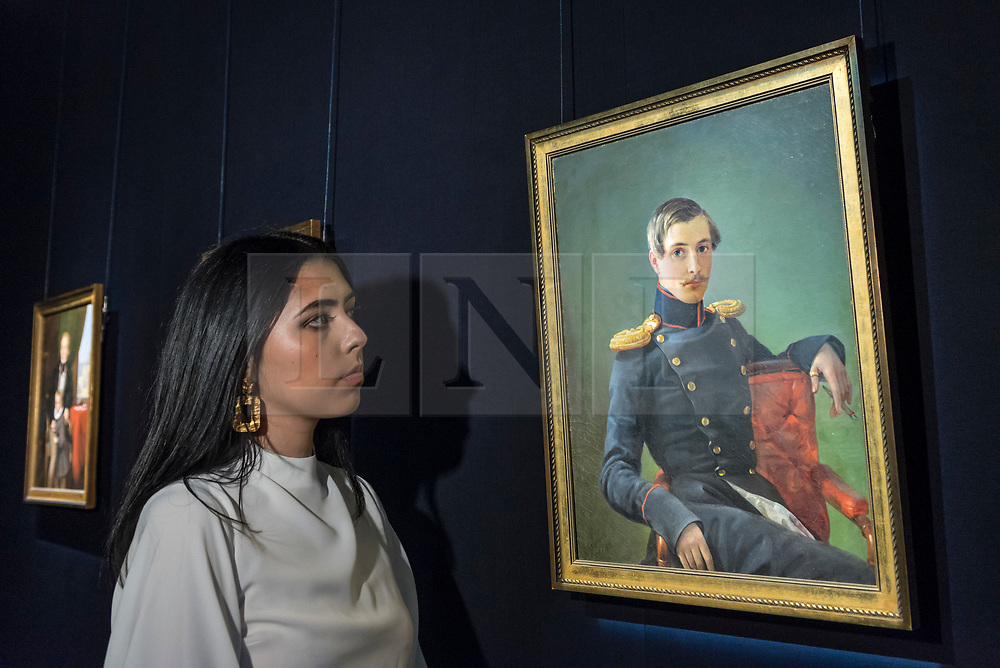 """© Licensed to London News Pictures. 31/05/2019. LONDON, UK. A staff member views """"Portrait of Alexander Nikolaevich Karamzin"""", 1839, by Pimen Nikitich Orlov (Est. GBP 25,000-35,000) at a preview of works from the upcoming sale of Russian Pictures, Works of Art, Fabergé & Icons Sales at Sotheby's, New Bond Street, on 4 June 2019.  Photo credit: Stephen Chung/LNP"""