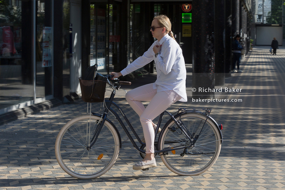 A lady cyclist rides along Slovenska Cesta (Street) in the Slovenian capital, Ljubljana, on 26th June 2018, in Ljubljana, Slovenia. Ljubljana is a small city with flat terrain and a good cycling infrastructure. It was featured at eighth on the 'Copenhagenize' index listing the most bike-friendly cities in the world.