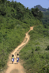 Two Girls walking the long road through hills to school, tallest girl Pengsee, smaller girl Seng, they do this journey everyday even when it is very bad weather.<br /> Teenpha village, Pha Oudom District, Bokeo Province, Lao PDR