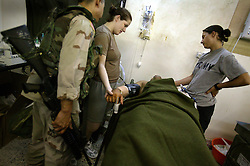 Soldiers from a neighboring unit visit the Charlie Med run by members of Company C, 407th Forward Support Battalion, 82nd Airborne Division, Baghdad, Iraq, Aug. 9, 2003. They comfort Ed Emad Eada, an Iraqi translator for the 82nd Airborne, recovers after he was shot for aiding Americans outside his home in Baghdad.