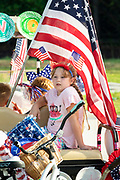 A young girl sits in the shade of an American flag during a hot day at the annual Independence Day golf cart and bicycle parade July 4, 2019 in Sullivan's Island, South Carolina. The tiny affluent Sea Island beach community across from Charleston holds an outsized golf cart parade featuring more than 75 decorated carts.