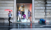 A woman walks past a clothing boutique in Rome as another begs on the corner.