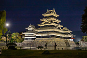 "Lit at night, Matsumoto Castle, built 1592-1614, in Matsumoto, Nagano Prefecture, Japan. Matsumoto Castle is a ""hirajiro"" - a castle built on plains rather than on a hill or mountain, in Matsumoto, Nagano Prefecture, Japan. Matsumotojo's main castle keep and its smaller, second donjon were built from 1592 to 1614, well-fortified as peace was not yet fully achieved at the time. In 1635, when military threats had ceased, a third, barely defended turret and another for moon viewing were added to the castle. Interesting features of the castle include steep wooden stairs, openings to drop stones onto invaders, openings for archers, as well as an observation deck at the top, sixth floor of the main keep with views over the Matsumoto city."