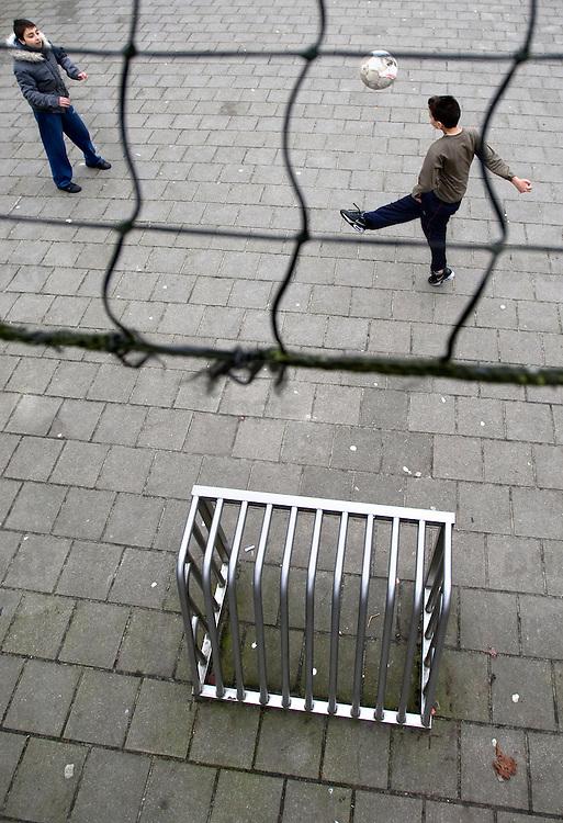 Nederland Amsterdam 22 februari 2009 20090222 Foto: David Rozing ..Straatvoetbal voetbalpleintje probleemwijk Kolenkitbuurt.Kids playing soccer on playground in deprived area, suburb..Foto: David Rozing ..
