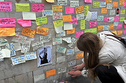 A woman leaves a message of support on the base of the obelisk on London Bridge, after an unknown 21 year-old man left a box of tape, sticky notes and marker pens with an invite to write a message, following the terror attack in which eight people died.