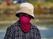 20 FEBRUARY 2019 - BAN LAEM, PHETCHABURI, THAILAND: A salt worker in a field on one of the first days of the 2019 salt harvest in Ban Laem, Thailand. Many of the workers cover their faces to protect them from the sun. Ban Laem's salt fields are expanding because salt harvesters in Samut Sakhon and Samut Songkhram,  which are closer to Bangkok, are moving to Ban Laem as their land is turned into industrial parks.     PHOTO BY JACK KURTZ