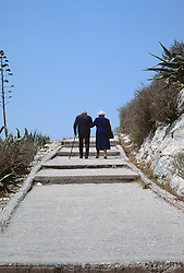 Older couple walking on a hillside with stairs