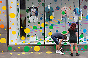 A man and woman pause outside the spotted-theme window display of Topshop on Oxford Street, on 2nd July 2019, in London, England.
