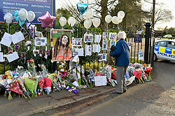 A woman stops to look at flower tribute left at scene of teenager's fatal stabbing in Chelmsoford Essex. December 2014