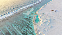 Aerial view of reclaimed land and calm waves breaking at the shore of local island Huraa, North Malé Atoll, Maldives, Indian Ocean