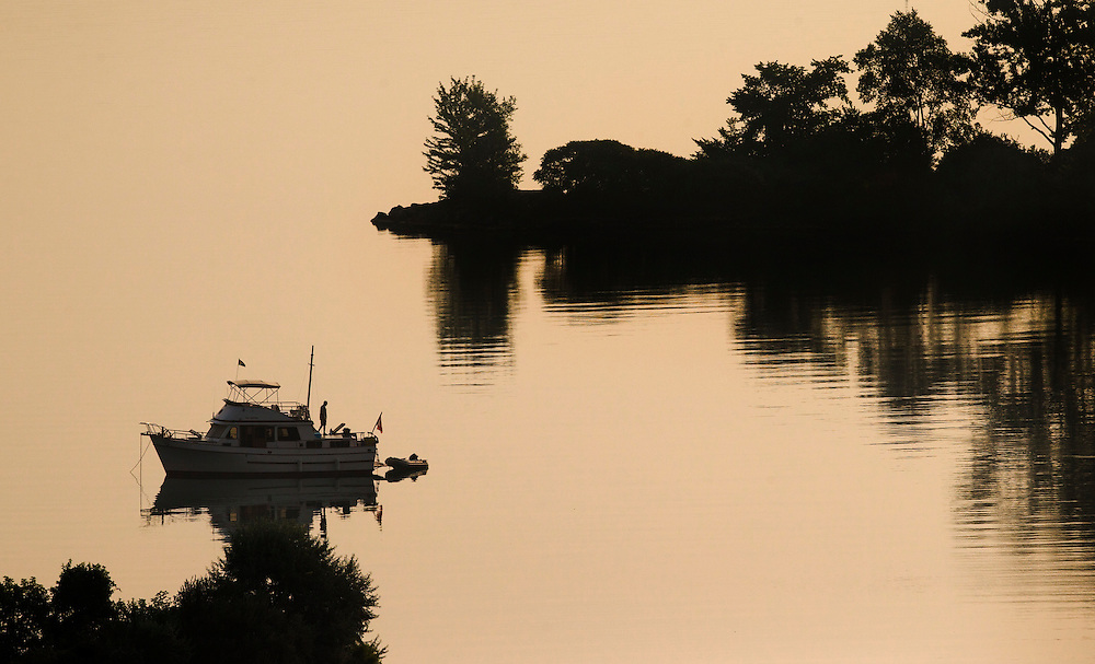 A man stands on his boat in Humber Bay on a warm morning in Toronto, September 3, 2015.    REUTERS/Mark Blinch