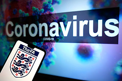 The FA England logo seen displayed on a mobile phone with an illustrative model of the Coronavirus displayed on a monitor in the background. Photo credit should read: James Warwick/EMPICS Entertainment