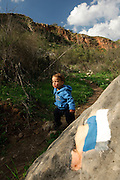 Israel, Galilee, Amud (Pillar) stream nature reserve and park A baby boy stands next to the blue trail marking