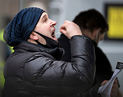 © Licensed to London News Pictures. 03/02/2021. London, UK. A member of the public self administers a COVID-19 test at a new Variant Testing Centre in Ealing, West London, set up after the discovery of a new South African variant of coronavirus. Door-to-door delivery of free home test kits is to start in the area in an attempt to slow the spread of the more aggressive strain of the virus. Photo credit: Ben Cawthra/LNP