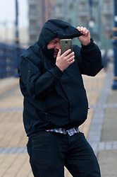 © Licensed to London News Pictures. 8/02/2016. Porthcawl, Bridgend, Wales, UK. A man struggles to take a selfie on the seafront. People struggle to stay on their feet in winds gusting over approximately 60mph. Storm Imogen batters the small Welsh seaside resort of Porthcawl in the county borough of Bridgend on the South coast of Wales, UK. Photo credit: Graham M. Lawrence/LNP