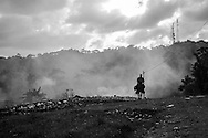 lone ranger: a man returns from work at the slaughter house up the road. men are notably absent from working at the rubbish tip, leaving it to the women and children.