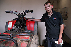 Man with Cerebral Palsy working as mechanic; standing next to all terrain vehicle in workshop,