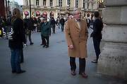 Gentleman wearing a camel coat turns a corner leading out of Piccadilly Circus in central London, UK.