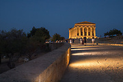 Landscape image with people walking toward the Temple of Concordia (Tempio della Concordia) at the Valley of Temples, Agrigento, Sicily, Italy.
