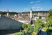 The Munothaldenweg / Munot pathway descends from the Munot's rose garden to the Old Town of Schaffhausen, in Switzerland, Europe. In the background rises the steeple of St. Johann Church on right. At left is the steeple of Münster zu Allerheiligen / All Saints' Minster, built in 1103 (replacing the first church built in 1049).