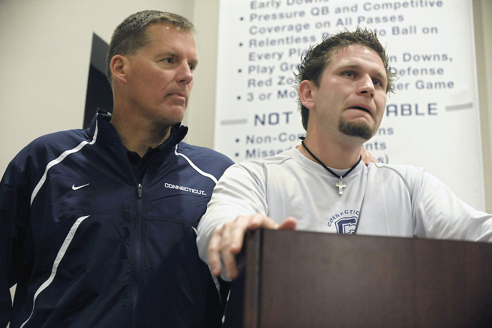Connecticut football head coach Randy Edsall, left, comforts senior captain Desi Cullen, right, during a news conference about the stabbing death of teammate Jasper Howard in Storrs, Conn.  Twenty-year-old Howard, of Miami, a junior and starting cornerback, and a second person were stabbed during a fight early Sunday after someone pulled a fire alarm during a dance at the UConn Student Union, police said.