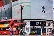 An image of a leaping figure from a Piccadilly Circus Calvin Klein ad whose slogan is 'Dare to Defy', and a London bus on 'Freedom Day'. This date is what Prime Minister Boris Johnson's UK government has set as the end of strict Covid pandemic social distancing conditions with the end of mandatory face coverings in shops and public transport, on 19th July 2021, in London, England.