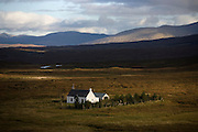 A crofter's cottage sits isolated in a deserted plain at Altnafeadh in Glencoe region, Scottish Highland Mountains.