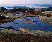 View of Sutton and Great Cranberry Islands beyond granite potholes on Cadillac Mountain, Mount Desert Island, Acadia National Park, Maine.