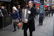Man carrying a tea urn along Charing Cross Road, London, UK. An unusual street scene in the West End.
