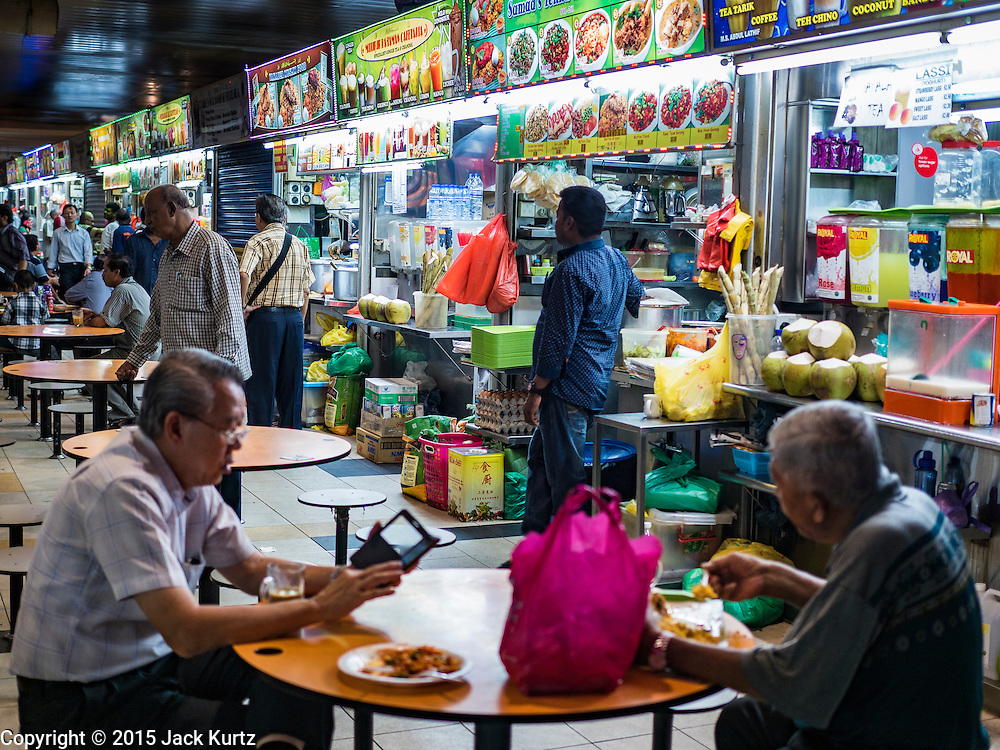 """27 DECEMBER 2015 - SINGAPORE, SINGAPORE:  People eat at the """"Hawker Stalls"""" in Tekka Market. First opened in 1915, the market was moved to its present location in 1982 and renovated in 2009. It is one of the most famous hawker stall (street food) areas in Singapore. Singapore moved the street food carts the city was famous for into markets and malls and created """"Hawker Stalls.""""     PHOTO BY JACK KURTZ"""