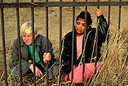 Friends age 16 looking through fence.  Minneapolis  Minnesota USA