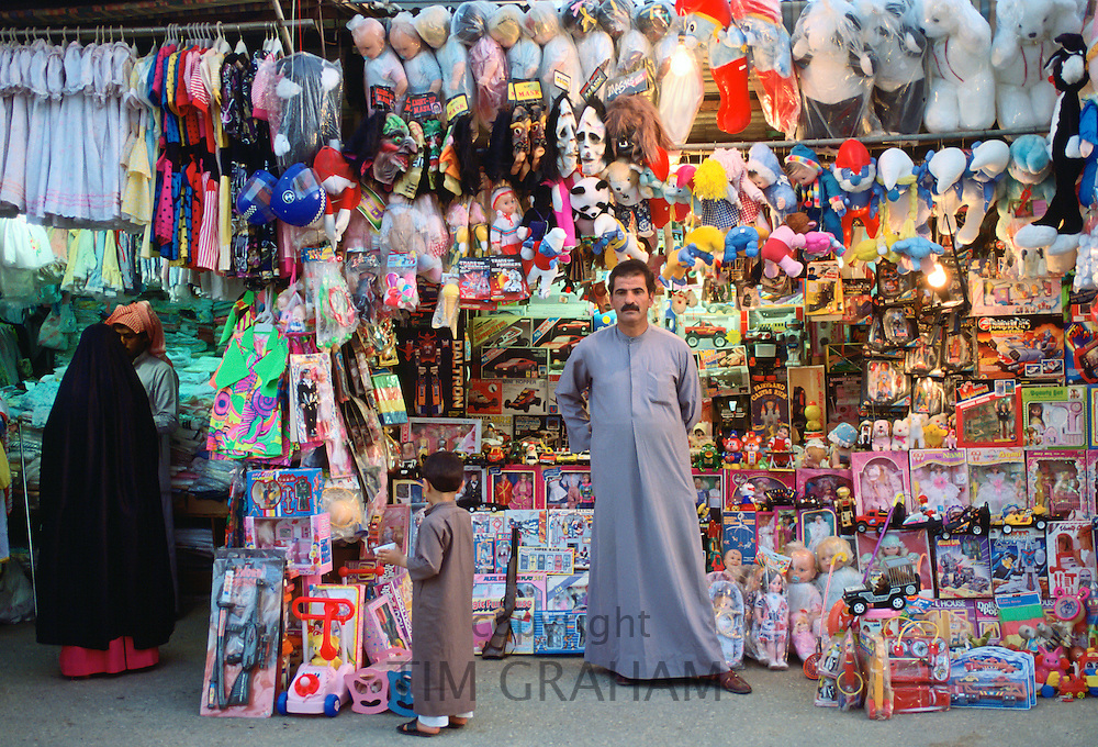 Small child gazing at toys in the market, Kuwait