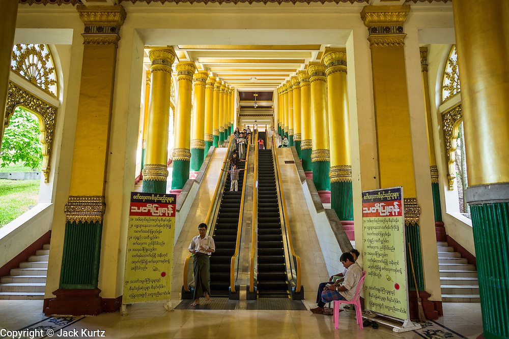 15 JUNE 2013 - YANGON, MYANMAR:  The west stairway into Shwedagon Pagoda. The Shwedagon Pagoda is officially known as Shwedagon Zedi Daw and is also called the Great Dagon Pagoda or the Golden Pagoda. It is a 99 metres (325ft) tall pagoda and stupa located in Yangon, Burma. The pagoda lies to the west of on Singuttara Hill, and dominates the skyline of the city. It is the most sacred Buddhist pagoda in Myanmar and contains relics of the past four Buddhas enshrined: the staff of Kakusandha, the water filter of Koṇāgamana, a piece of the robe of Kassapa and eight strands of hair fromGautama, the historical Buddha. The pagoda was built between the 6th and 10th centuries by the Mon people, who used to dominate the area around what is now Yangon (Rangoon). The pagoda has been renovated numerous times through the centuries. Millions of Burmese and tens of thousands of tourists visit the pagoda every year, which is the most visited site in Yangon.  PHOTO BY JACK KURTZ