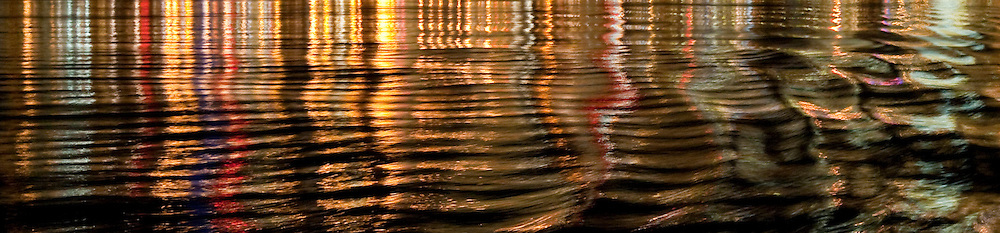 Seattle Lights reflecting on Puget Sound, WA, USA with ripples added from the Washington State Ferry (panorama)