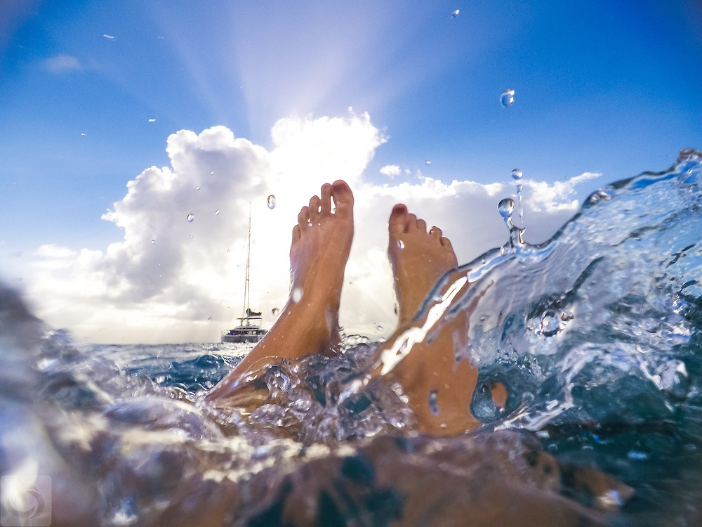 First person POV of a pair of young woman's feet while swimming in clear waters in Guadeloupe of the French Caribbean