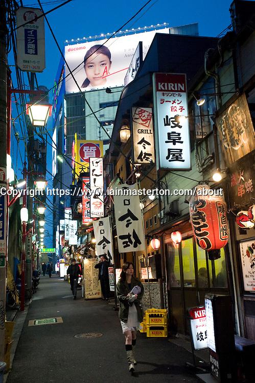 Night view of narrow street lined with bars and restaurants in Shinjuku Tokyo Japan