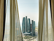 Intimate view through curtain, from a hotel room looking over the futuristic Etihad Towers.