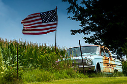 1960's era Ford Falcon sits along a rural driveway with an American Flag flying nearby.