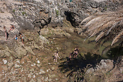 Aerial view of beachcombers as they explore rock pools in Cascais, near Lisbon, Portugal.