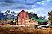 A moody, artistic image of a pending storm rolling in over the Grand Tetons and a historic barn in Jackson Hole, WY.