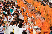 """Sept. 26, 2009 -- PATTANI, THAILAND:  Buddhist monks walk through the crowd accepting donations of food during the Tak Bat Sankatan ceremony in Pattani, Thailand Saturday. Buddhists in Thailand's three southern most provinces gathered in Pattani Saturday, Sept 26 to celebrate Tak Bat Sankatan, the day Lord Buddha returned to earth and was greeted by a crawd of his disciples and Buddhist believers who were waiting to offer him food. Buddhists monks representing the 266 """"Wats"""" (temples) in the three provinces (Pattani, Narathiwat and Yala) processed through the crowd and were presented with food and gifts.   Photo by Jack Kurtz"""