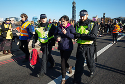 London, UK. 17th November, 2018. Police officers arrest a woman after environmental campaigners from Extinction Rebellion blocked Lambeth Bridge, one of five bridges blocked in central London, as part of a Rebellion Day event to highlight 'criminal inaction in the face of climate change catastrophe and ecological collapse' by the UK Government as part of a programme of civil disobedience during which scores of campaigners have been arrested.