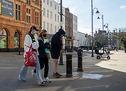 25th February 2021. Friends take a walk during the third national lockdown in Cheltenham High Street.