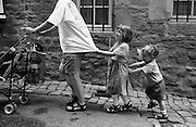 """A four year-old girl pulls at her mother's t-shirt as she pushes a pushchair uphill while her two year-old brother in turn pushes her up the incline of a street in Rennes, Brittany, France. In order of size - from tallest to smallest, they march together up the gradient of this French street, they laugh at this great game of push and pull. The three are on holiday in this town, during a vacation to Britanny. From a personal documentary project entitled """"Next of Kin"""" about the photographer's two children's early years spent in parallel universes. Model released."""