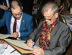 Old Town Hall, Stratford, London - 28 November 2015. Singers Marc Almond, Ronan Parke, Heather Peace and Asifa Lahore headline the Peter Tatchell Foundation's inaugural Equality Ball, a fundraiser for the foundation's LGBTI and human rights work, with guest of honour Sir Ian McKellen  joined by Paul O'Grady, Rupert Everett and Michael Cashman. PICTURED:  As Ed Fordham looks on (L) Sir Ian McKellen signs a musical score for Lord of the Rings to be raffled. //// FOR LICENCING CONTACT: paul@pauldaveycreative.co.uk TEL:+44 (0) 7966 016 296 or +44 (0) 20 8969 6875. ©2015 Paul R Davey. All rights reserved.