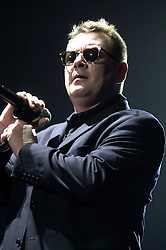Carl Smyth of Madness at Sheffields Hallam FM Arena. The show was stopped for around 30 minutes after the first three songs, when over enthusiastic fans mannaged to throw beer over the mixing desk causing the sound system to fail. Staff at the Hallam FM Arena Came to the rescue with the hair dryer which was used to dry out soggy sound system and Madness went on to play the whole Show<br /> 11 December 2003<br /> <br /> image copyright Paul David Drabble