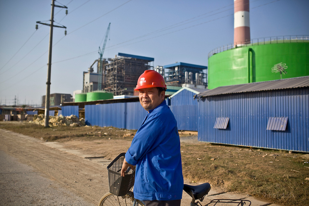 A Chinese worker rides bicycle near the Haiphong Thermal Power Plant construction site in Trung Son, Vietnam, Nov. 21, 2009. Dongfang Electric, a large Chinese contractor, and Marubeni, a Japanese company, won the $500-million contract in 2005. China, famous for its export of cheap goods, is increasingly known around the .world for shipping out cheap labor.